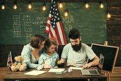 Home school. Kid with parents in classroom with usa flag, chalkboard on background. American family sit at desk with son. And usa flag. Parents teaching son Stock Photos