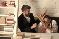 Home schooling. Girl with glasses and bearded man fight with scrolls. Home schooling. Girl with glasses and bearded men sit at desk and fight with scrolls royalty free stock photography