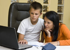 Home schooling with laptop. Mother and her teenage boy doing school homework. They are serious and looking at the laptop computer screen, looking for information Royalty Free Stock Photo