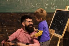 Home schooling. Smiling daddy teaching his son new skills. Father and son looking at each other with love. Standing kid. Hugging his sitting dad. Home education Stock Image