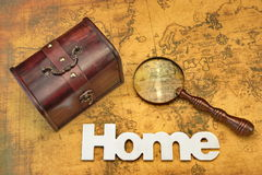 Home Search Or Emigration Concept. Bag Or Storage Box, Wooden Sign Home And Magnifier On the Old Map Background, Top View, Close Up royalty free stock image