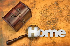 Home Search Or Emigration Concept. Bag Or Storage Box, Wooden Sign Home And Magnifier On the Old Map Background, Top View, Close Up stock photos
