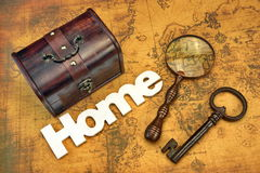 Home Search Or Emigration Concept. Bag Or Storage Box, Wooden Sign Home And Magnifier On the Old Map Background, Top View, Close Up stock photography