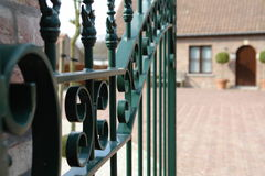 Home Security. Open wrought iron gate leading to a home.  Focus on gate Stock Photos