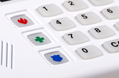 Home security alarm keypad with emergency buttons. Closeup of home security alarm keypad with fire, police, and medical emergency buttons, shallow depth of field Royalty Free Stock Images