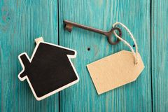 Home security concept. Little house and old key real renting keychain property moving wooden unlock door business table estate access success landlord agent stock images