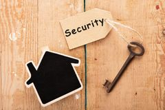 Home security concept. Little house and old key with tag stock photography