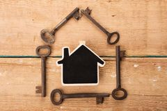 Home security concept. Little house and old keys real renting property moving wooden unlock door business table estate access success landlord agent buy stock photo