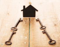 Home security concept. Little house and old keys real renting property moving wooden unlock door business table estate access success landlord agent buy stock image