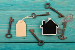 Home security concept. Little house and old keys real renting keychain property moving wooden unlock door business table estate access success landlord agent stock photo