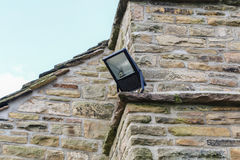 Home security light mounted on the corner of a rural stone cotta. Ge Stock Images