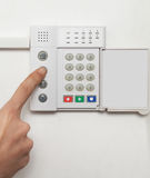 Home security. Setting up a security alarm on a white wall Stock Image