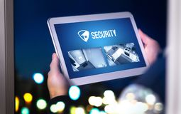 Home security system and application in tablet. Man watching protection camera live footage inside a house or apartment late at night. Imaginary smart app Royalty Free Stock Images
