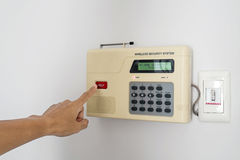 Home security system with hand pushing red button Royalty Free Stock Photos