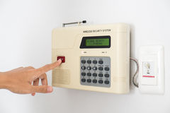 Home security system with hand pushing red button Stock Photos