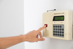 Home security system with hand pushing red button Stock Images