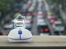 Home service concept. Hammer and wrench and house icon with wireless computer mouse on wooden over blur of rush hour with cars and road, Home service concept Stock Images