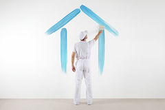 Home service concept. painter man with brush drawing a blue house. Isolated on the blank white wall Royalty Free Stock Photography