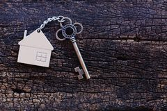 Home shape keyring with antique key on old wooden table. Welcome to new home, home sweet home concept. Copy space. Home shape keyring with antique key on old stock images