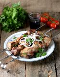 Home shish kebab from pork on skewers with pickled onion and parsley on an old wooden background. Food Royalty Free Stock Photos