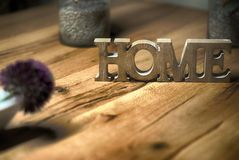 Home sign balanced on wooden table contrast- rest and relaxation Royalty Free Stock Photos