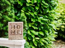 Home sign with a green garden in the background royalty free stock image
