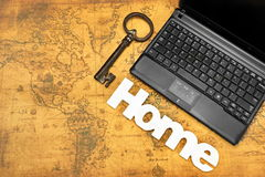 Home Sign, Key And Laptop On Old Map Background Stock Photos