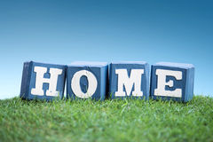 HOME sign made of wooden blocks on a grass Stock Photography