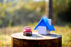 Home and small toy car. Put on the log In the woods and mountain stock photography