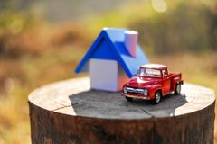 Home and small toy car. Put on the log In the woods and mountain stock image