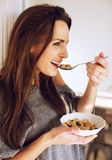 At Home with Smiling Woman Eating Breakfast. Portrait of a smiling woman at home eating her breakfast stock image