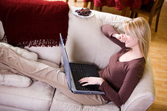 At Home: Smiling Woman Uses Laptop While Relaxing On Couch Royalty Free Stock Photo