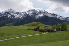 Home on Snow capped mountains with green hills Stock Images
