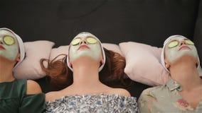 Home spa drie vrouwen die stukken van komkommer op hun gezichten houden die op het bed liggen Het concept van de schoonheidssalon stock videobeelden