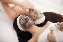 Home spa. Two beautiful young women holding pieces of cucumber o. N their eyes and smiling while on the bed royalty free stock photos