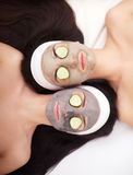 Home spa. Two beautiful young women holding pieces of cucumber on their eyes and smiling while on the bed Stock Images