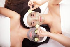 Home spa. Two beautiful young women holding pieces of cucumber on their eyes and smiling while on the bed Stock Photos