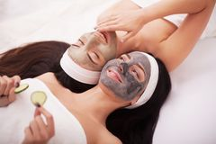 Home spa. Two beautiful young women holding pieces of cucumber on their eyes and smiling while on the bed.  stock photos