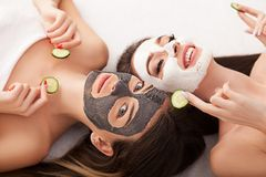 Home spa. Two women holding pieces of cucumber on their faces ly Royalty Free Stock Image
