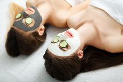 Home spa. Two women holding pieces of cucumber on their faces lying the bed. Home spa. Two women holding pieces of cucumber on their faces lying the bed royalty free stock photos