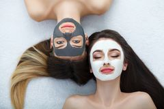 Home spa. Two women holding pieces of cucumber on their faces lying the bed. royalty free stock image