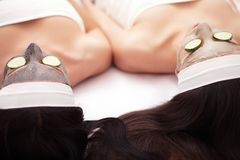 Home spa. Two women holding pieces of cucumber on their faces lying the bed. Home spa. Two women holding pieces of cucumber on their faces lying the bed royalty free stock photography