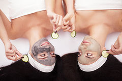 Home spa. Two women holding pieces of cucumber on their faces lying the bed. Stock Photo