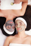Home spa. Two women holding pieces of cucumber on their faces lying the bed. Royalty Free Stock Photography
