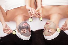 Home spa. Two women holding pieces of cucumber on their faces lying the bed. Stock Images