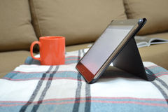 Home stay. Tablet, a cup and a plaid Stock Image