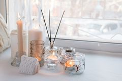 Home still life in the interior with collection of candle stick and aroma stick,on the windowsill, a cozy home decor, the concept. Of home items, white stock images