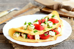 Home stuffed omelet on a plate. Egg omelet with a filling of fresh cherry tomatoes, cheese and parsley Royalty Free Stock Photos
