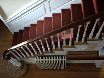 Home: sunlit staircase with red carpet. Sunlit staircase with red carpet in historic home Stock Photo