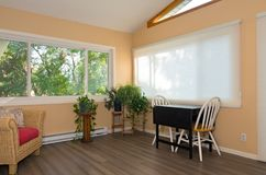 Home Sunroom Interior and Decor. Interior of remodeled sunroom addition to home and decor including small table with chairs bamboo flooring and view from window stock photos